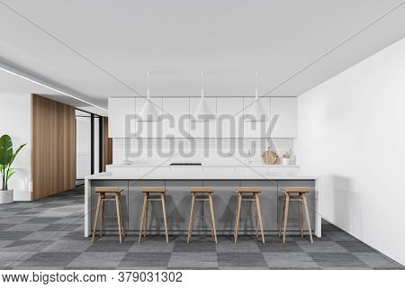 Interior Of Modern Kitchen With White And Wooden Walls, Carpeted Floor, White Cupboards And Bar With