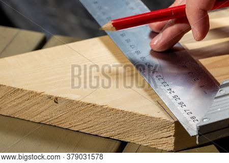 A Closeup Portrait Of Someone Using A Stainless Steel L-square Or Snag To Measure And Draw A Perfect