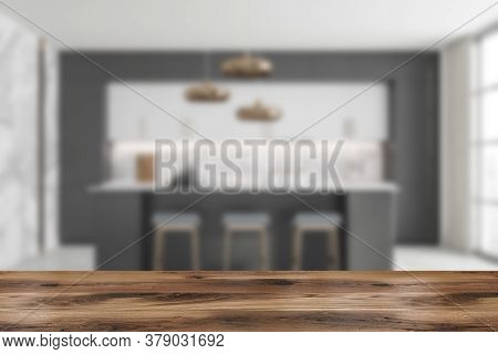 Wooden Table For Your Product In Blurry Stylish Kitchen With Gray And Marble Walls, White Cupboards