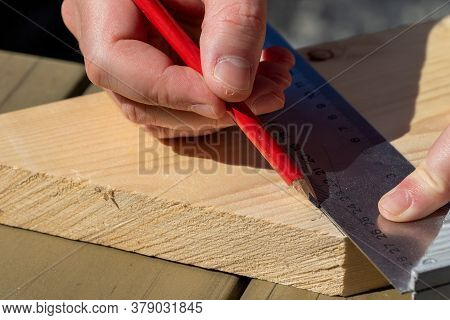 A Closeup Portrait Of A Man Using A Pencil And A Stainless Steel L-square Or Snag To Draw A Perpendi