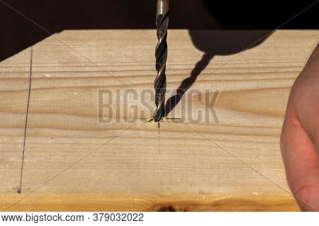 A Closeup Portrait Of A Person Drilling A Hole In A Wooden Plank On The Drawn Pencil Marking. The Wo