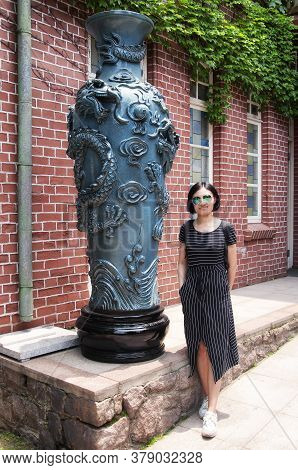 A Smiling Chinese Woman Wearing A Pinstripe Dress Standing Next To A Large Dragon Covered Vased With