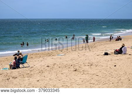 July 30, 2020 In Newport Beach, Ca:  Beachgoers Sunbathing On The Sandy Beach And Swimming In The Oc