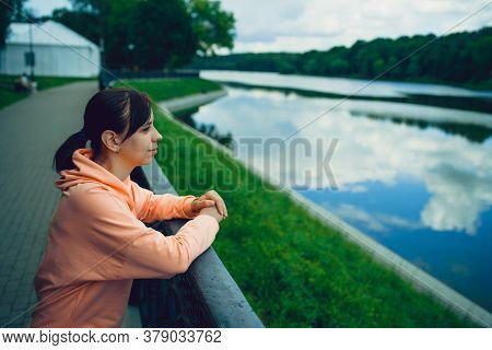 Portrait Of Young Woman Standing On Waterfront. Close Up Of Female Looking Away, Enjoying Beautiful