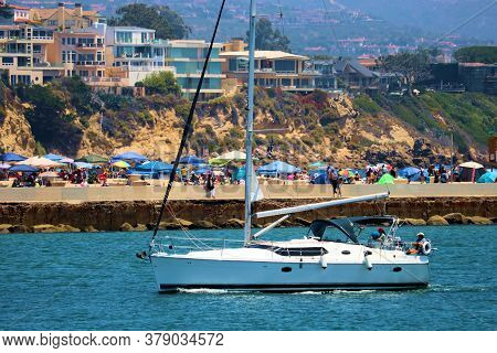 July 30, 2020 In Newport Beach, Ca:  Crowds Of People Relaxing On The Sandy Beach With A Sail Boat R