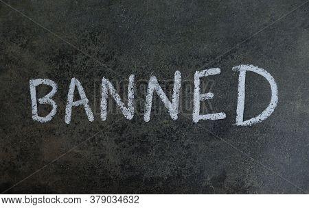 Banned Word Written On Blackboard With White Chalk