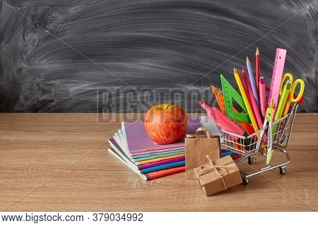 Shopping trolley with stationery accessories and boxes on wooden table on background of school blackboard with copy space. School accessories for education and development. Preparation for school