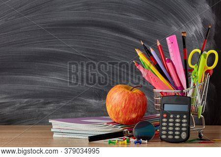 Shopping trolley with stationery accessories and calculator on wooden table on background of school blackboard with copy space. Preparation for school, planning budget. Cost of education