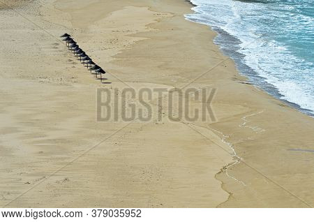 A Row Of Eleven Sunshades On The Beach In Odeceixe On The Atlantic Coast Of Portugal