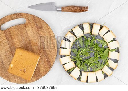 Sliced Smoked Cheese With Rucola On The Plate