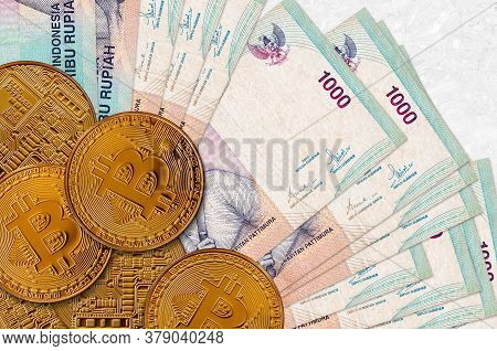 1000 Indonesian Rupiah Bills And Golden Bitcoins. Cryptocurrency Investment Concept. Crypto Mining O