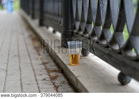 Close Up Of Disposable Cup With Beer Stands On Concrete On Waterfront. Alcoholic Beverage Forsaken I