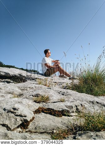 The Guy Dreamily Looks Into The Distance, Sitting On The Stones Against The Background Of The Sky. H