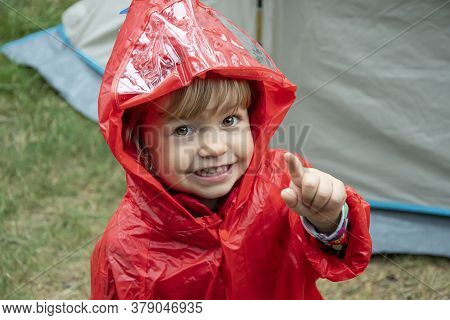 A Little Girl In A Red Raincoat With A Hood Points Up At A Tourist Camp Against The Background Of A