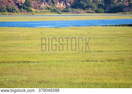 Grasslands Besides A River With Bluffs Beyond Taken On An Estuary At The Newport Back Bay In Newport