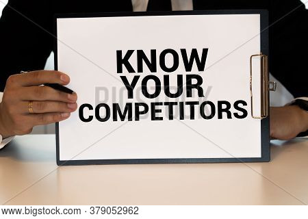 Closeup On Businessman Holding A Card With Text Know Your Competitors, Business Concept Image With S