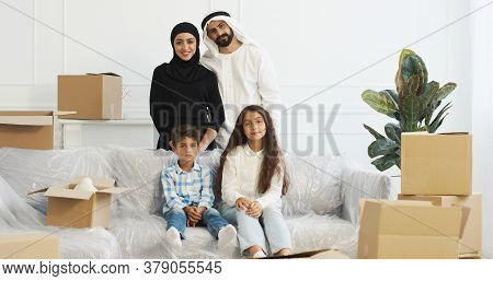 Portrait Of Happy Muslim Family Smiling To Camera And Posing In Living Room. Moving In New Accommoda