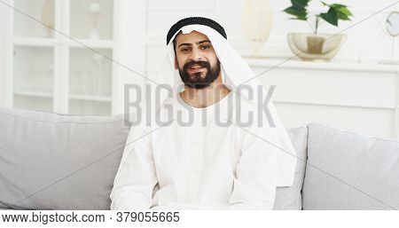 Portrait Of Handsome Young Arabian Man In Kandura Sitting On Couch In Living Room And Smiling To Cam