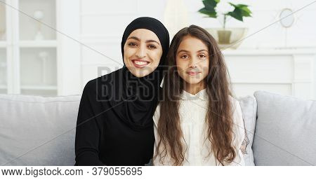 Portrait Of Beautiful Young Muslim Mother In Headscarf Smiling To Camera While Sitting With Cute Tee
