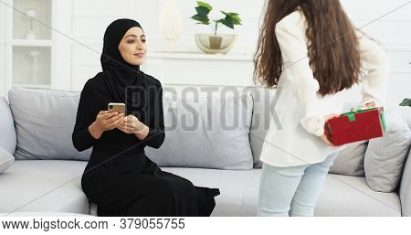 Daughter Coming To Muslim Mother In Hijab With Present Behind Back. Arabian Woman In Abaya Dress Sit