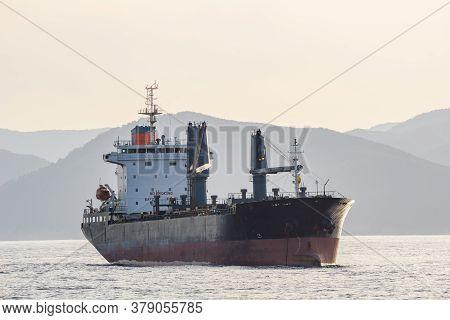 An Old Bulk Carrier Or Bulker Sails In The Sea Near Shore.