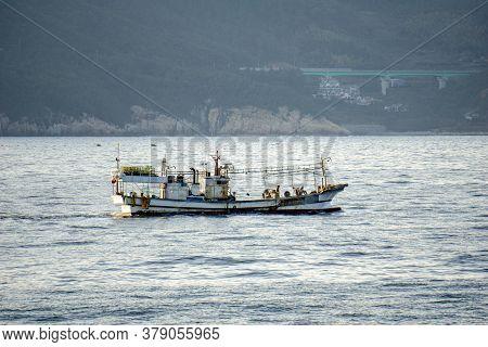 Korean Fishing Boat Sails Pass Shore Line In The Internal Waters Territory.