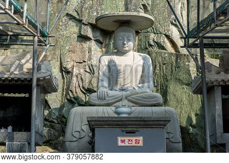 Busan, South Korea - July 20, 2017 : Ancient Sitting Buddha Wearing A Hat Image Statue  Stone Sculpt