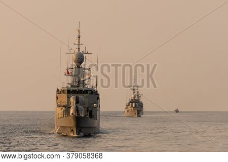 Navy Warship Fleet Underway In Formation In The Sea When Sundown.