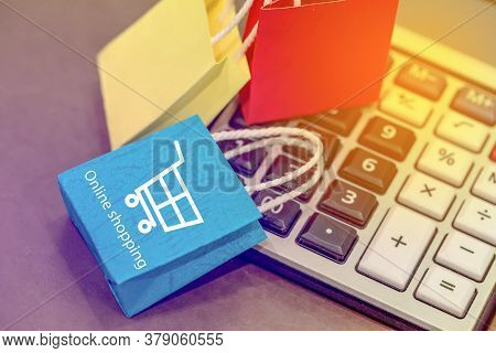 Closeup Shot Of Blue Color Paper Shopping Bags On A Calculator. Business Concept For Discount Prices