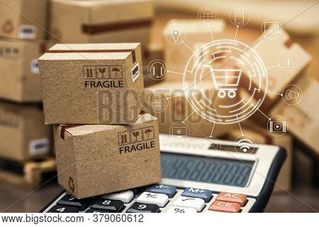 Business Finance: Packaging Small Paper Boxes On Wood Pallet With Calculator. Ideas For Assembling A