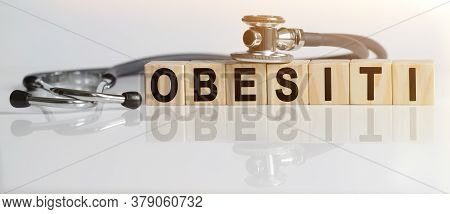 Obesitythe Word On Wooden Cubes, Cubes Stand On A Reflective White Surface, On Cubes - A Stethoscope