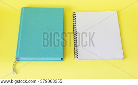 Blank Notepad On Yellow Table, Next To Turquoise Notepad. Business Concept