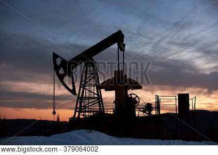 View Of Evening Dramatic Sky Over Long Stroke Balanced Beam Petroleum Pump Jack. Oil Field With Oil