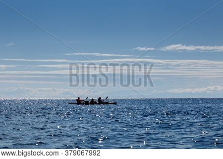 Baikal Lake, Russia - July 19 2020: Canoe Rowers At Lake At Sunny Day With Blue Sky And Clouds