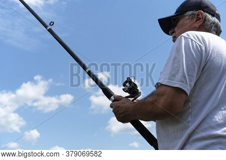 Fishing In River.a Fisherman With A Fishing Rod On The River Bank. Man Fisherman Catches A Fish.fish