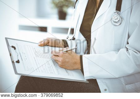 Unknown Woman-doctor Writing Something At Clipboard While Sitting At The Chair, Close-up. Therapist
