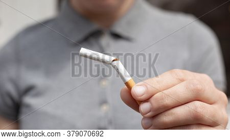 Broken Cigarette In Hand Close-up. Bad Habit, Stop Smoking, The Harm From Smoking Tobacco And Nicoti