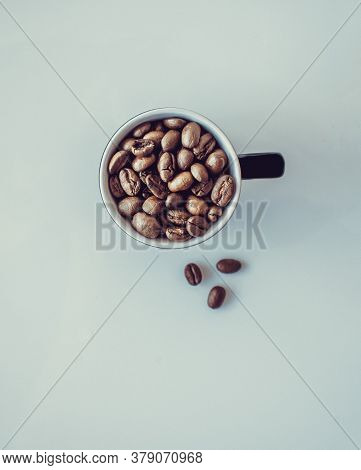Coffee Beans Falling In White Coffee Cup. Highspeed Shot, A Cup With Coffee Beans On White Backgroun