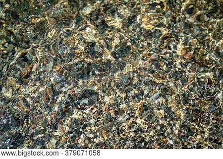 The Texture Of The Bottom. Many Small Stones Are Visible Under The Clear Water. Water Ripples Of The