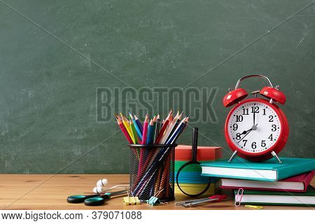 Back To School Or Education Concept With Alarm Clock, Paper Notebooks And School Supplies Against Bl
