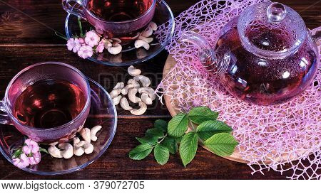 Green Tea Leaves Or Leaves Of Medicinal Herbs Lie On The Table With A Teapot And Mugs Of Red Tea, Ca