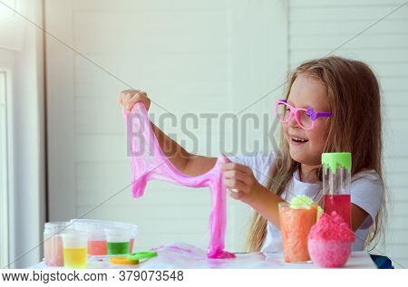 Little Girl Stretching Pink Slime To The Sides. Kids Hands Playing Slime Toy.