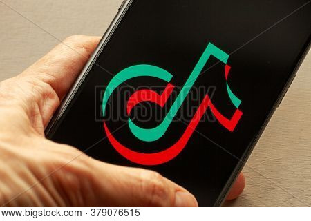 Tiktok Application Icon On Apple Iphone 11 Screen Close-up. Hand Holding Smartphone With Tik Tok Ico