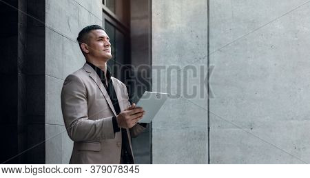 Portrait Of A Young Striving Ceo Or Leader Working On Tablet.  Businessman Standing At The City And