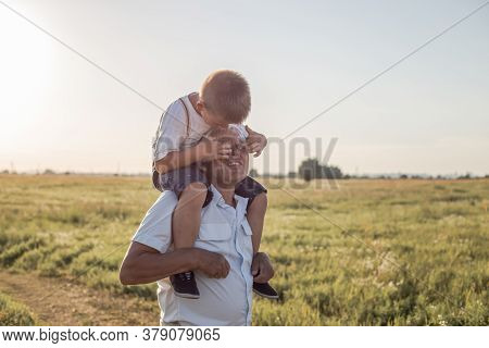 Grandfather Carrying Grandson For A Piggyback Ride In Teh Neighborhood. Happy Senior Man Smiling Whi