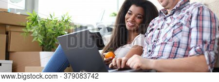 Portrait Of Wonderful Afro-american Woman With Smiling Man Looking At Laptop With Gladness. Couple I