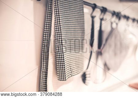 Closeup Of Textile Napkin Hanging On Metal Railing With Assorted Utensils Near Wall In Contemporary