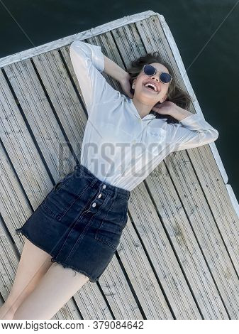 Side View Of Young Carefree Female Wearing Trendy Clothes And Sunglasses Relaxing On Wooden Quay In