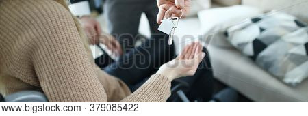 Close-up Of Male Businessman Giving Keys From New House To Disabled Woman. Female Sitting In Wheelch