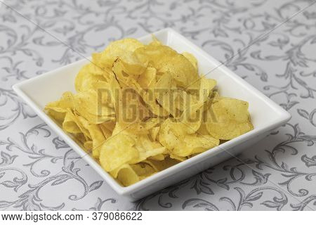 Potato Chips Sprinkled On A White Plate.